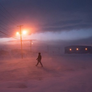 A figure walks through the blustery night in Pond Inlet.