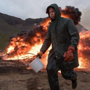 A local feeds a bonfire with diesel fuel in northern Iceland.